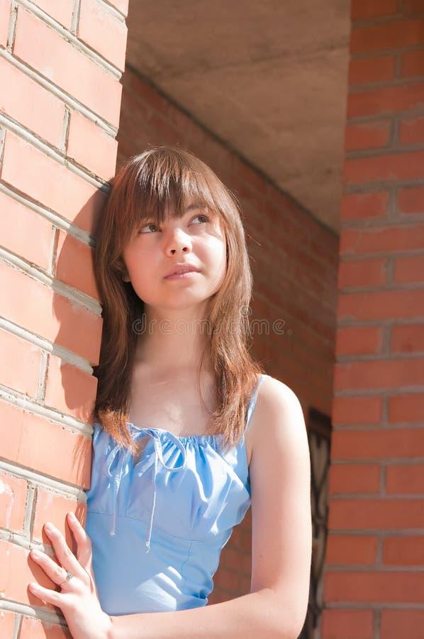 La ragazza ad un muro di mattoni immagini stock libere da diritti