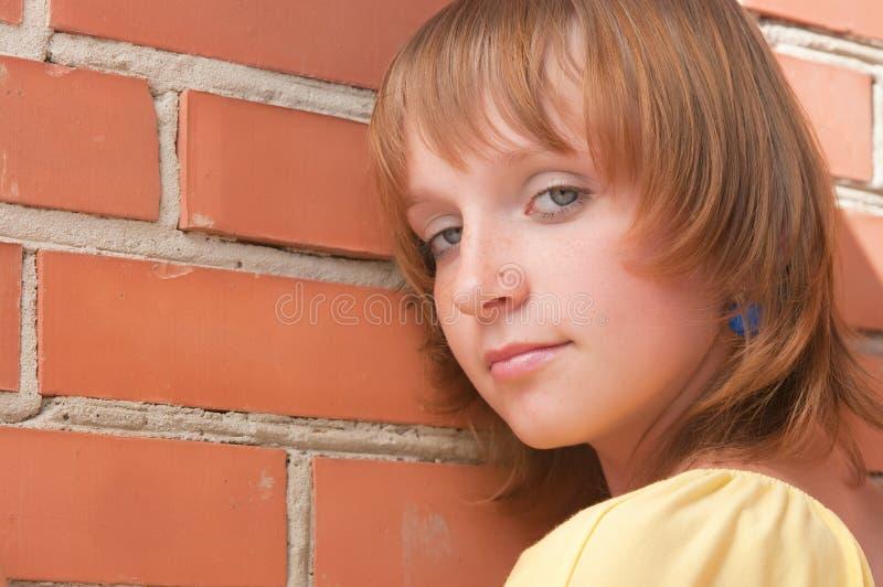 La ragazza ad un muro di mattoni fotografie stock