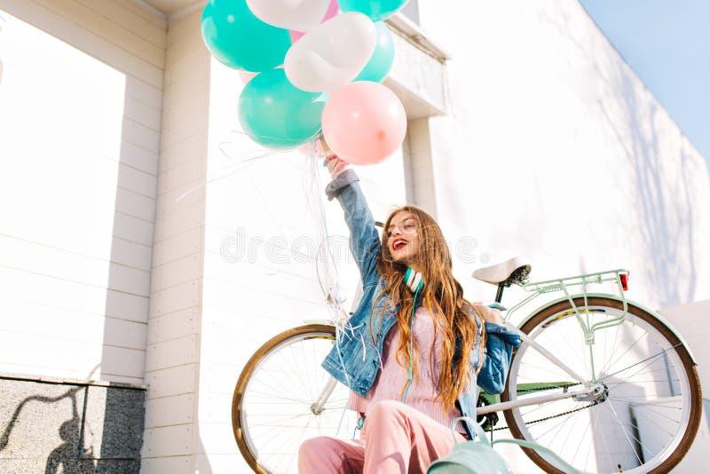 La ragazza affascinante alla moda con capelli marroni si rallegra la vita, sollevante la mano con un mazzo di palle colorate Giov fotografia stock libera da diritti