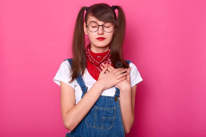 La ragazza affascinante snella con gli occhi chiusi sta l'incrocio diritto entrambe le mani sul petto, provante a ritenere il bat fotografia stock libera da diritti