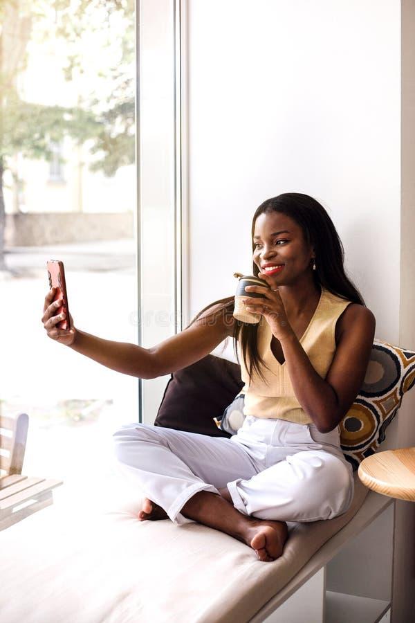 La ragazza africana attraente fa il selfie al davanzale al caffè fotografia stock libera da diritti