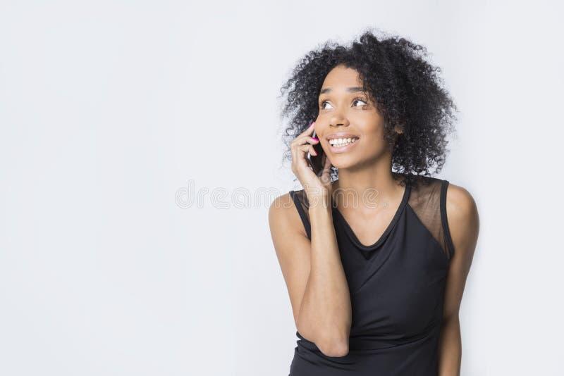 La ragazza africana sorridente sta parlando sul suo telefono cellulare immagine stock