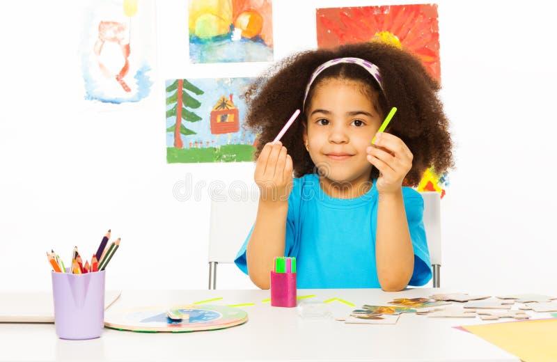 La ragazza africana tiene i coni retinici di cuisenaire impara contare immagini stock
