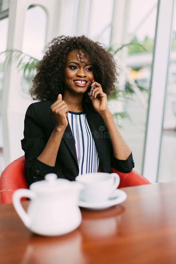 La ragazza afroamericana alla moda vestita sta parlando tramite cellulare nel caffè immagini stock