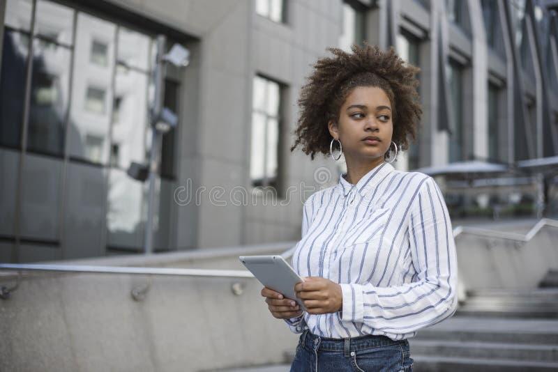 La ragazza afroamericana sta vicino ad un edificio per uffici e tiene un computer della compressa in sue mani fotografia stock