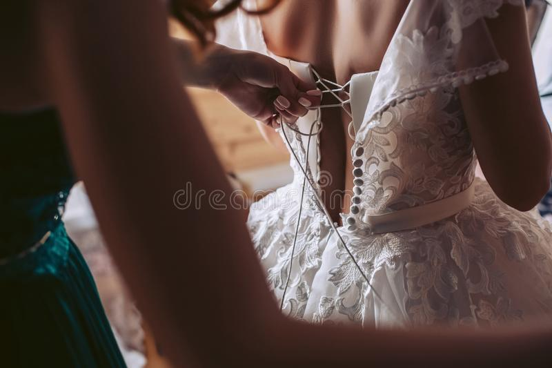 La ragazza aiuta la sposa al vestito da sposa da bianco di vestito fotografia stock libera da diritti