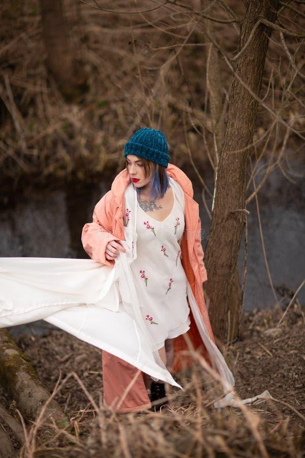 La ragazza alla moda cammina lungo il fiume, vicino ad un piccolo ponte di legno fotografia stock libera da diritti
