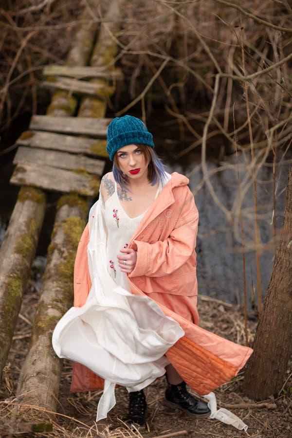 La ragazza alla moda cammina lungo il fiume, vicino ad un piccolo ponte di legno immagini stock libere da diritti