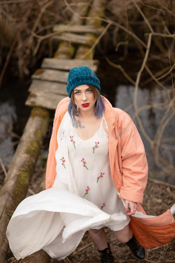 La ragazza alla moda cammina lungo il fiume, vicino ad un piccolo ponte di legno fotografie stock libere da diritti