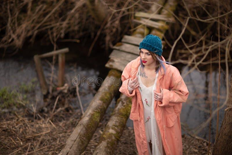 La ragazza alla moda cammina lungo il fiume, vicino ad un piccolo ponte di legno immagini stock
