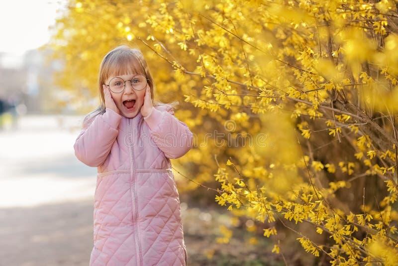 La ragazza alla moda del bambino 5-6 anni che portano il cappotto rosa d'avanguardia in autunno parcheggia esaminando macchina fo fotografia stock libera da diritti
