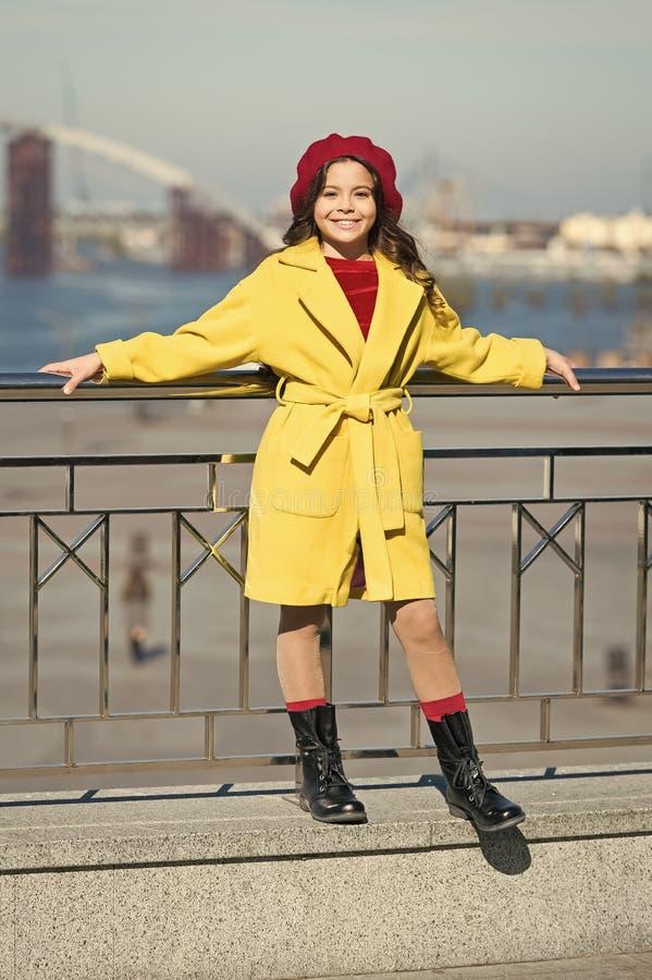 La ragazza alla moda gode della passeggiata il giorno di molla soleggiato Berretto luminoso del cappello del bambino e cappotto c immagini stock libere da diritti