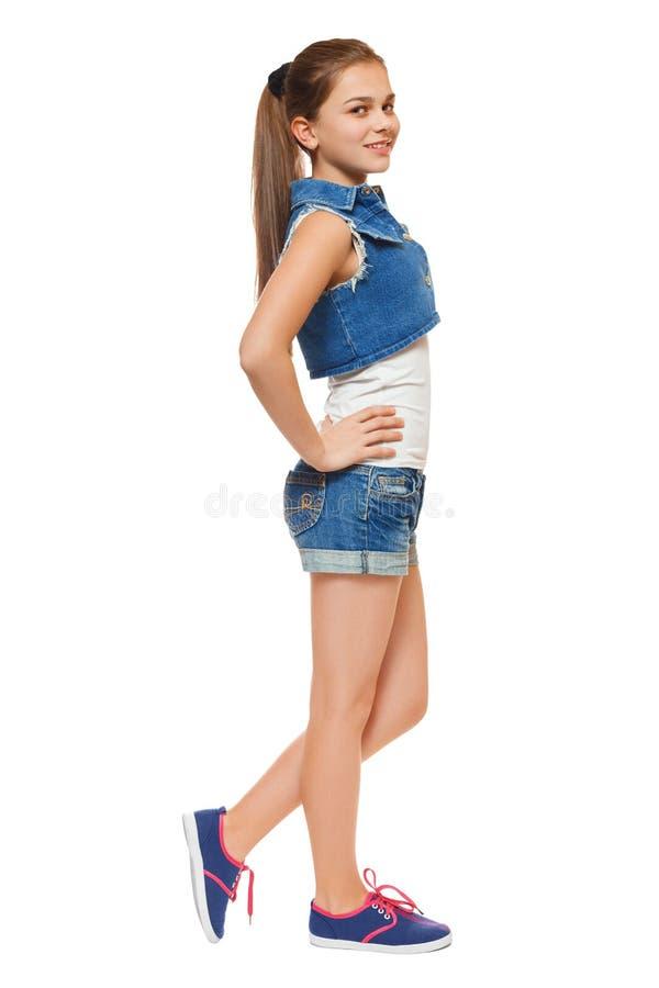 La ragazza alla moda in jeans conferisce a e shorts del denim Adolescente di stile della via, stile di vita, isolato su fondo bia fotografie stock