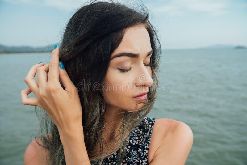 La ragazza alla moda triste dei pantaloni a vita bassa raddrizza le bande contro lo sfondo del mare in Asia fotografia stock libera da diritti