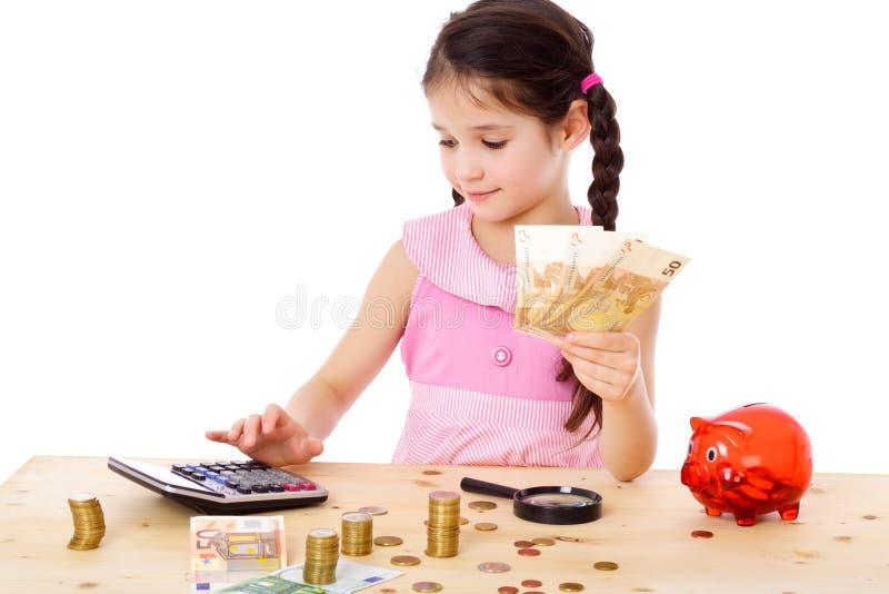 La ragazza alla tavola conta i soldi fotografia stock