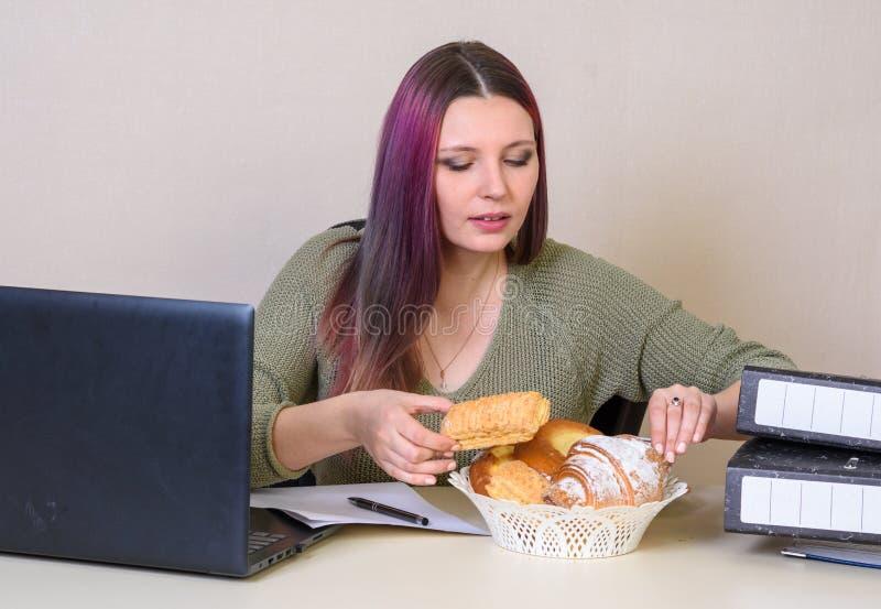 la ragazza alla tavola nell'ufficio prende un croissant da un piatto con le pasticcerie fotografia stock