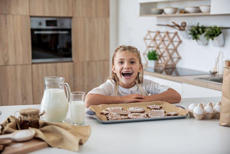 La ragazza allegra è soddisfatta con la pasticceria auto-al forno di Natale immagine stock libera da diritti