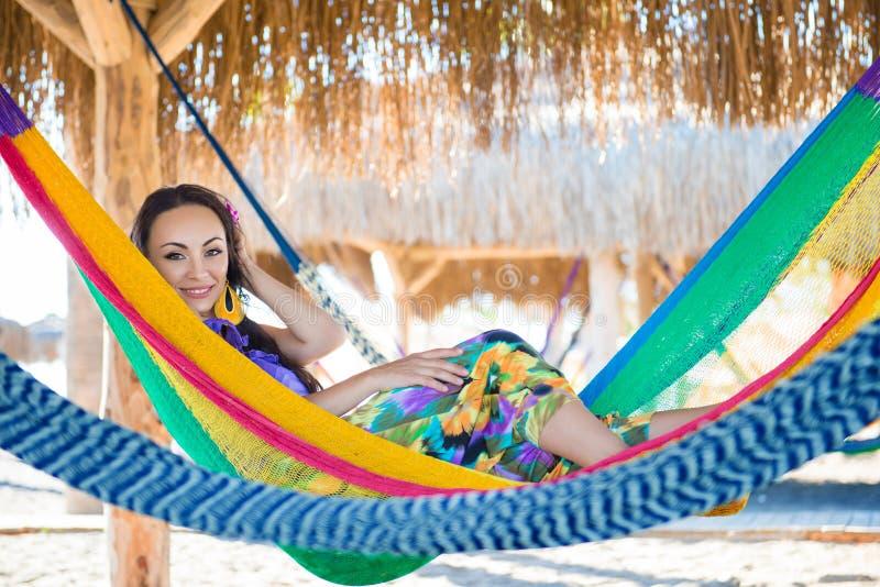 La ragazza allegra abbastanza sorpresa sulla spiaggia, sorridente si trova in un'amaca contro il contesto delle palme, stile di v immagine stock