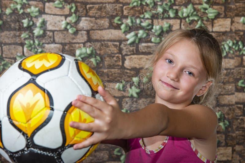 La ragazza allegra e felice mostra un pallone da calcio e esamina la macchina fotografica immagini stock