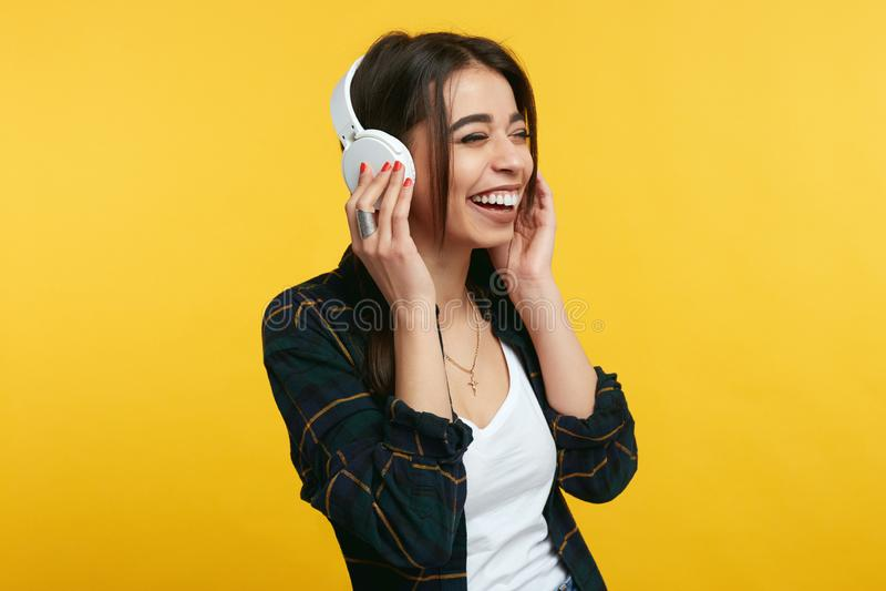 La ragazza allegra gode del suono di musica, tiene le mani sulle cuffie, chiude gli occhi da piacere, sopra fondo giallo fotografia stock libera da diritti