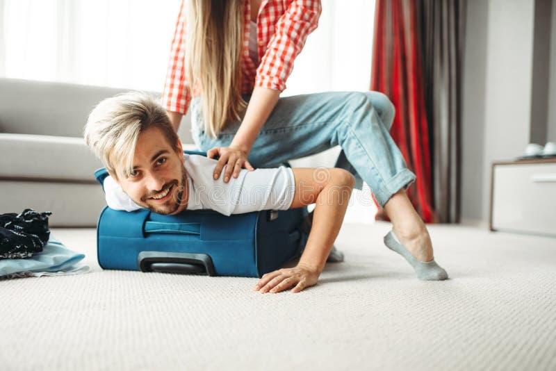 La ragazza allegra ha imballato il suo marito in una valigia immagini stock