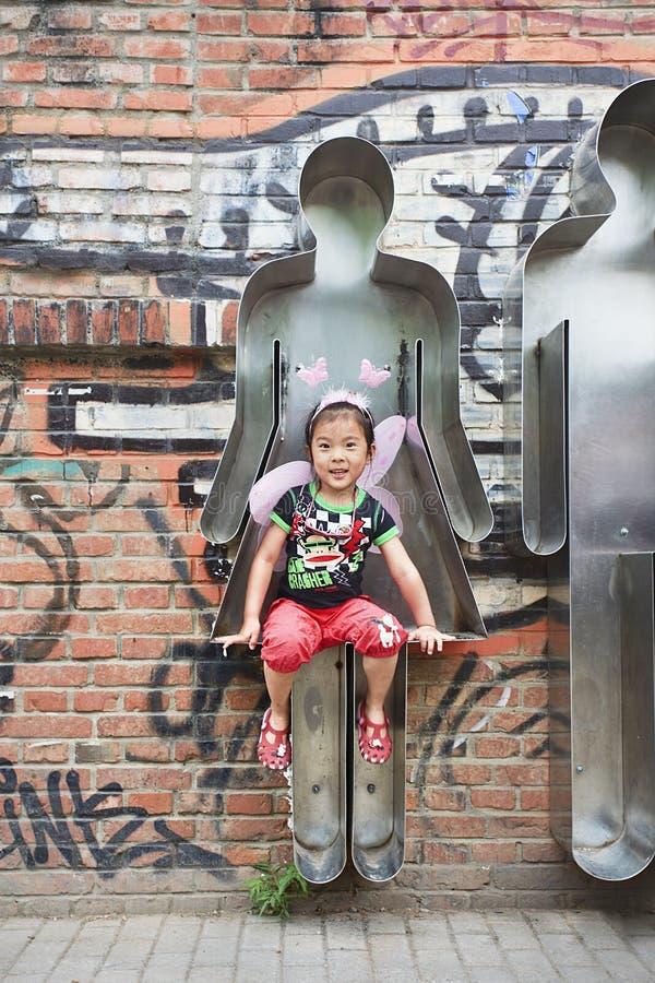 La ragazza allegra si siede in un'opera d'arte ad un'area di 798 arti, Pechino, Cina fotografia stock