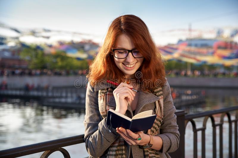 La ragazza allegra sorridente fa una nota in un taccuino, progettante come t fotografia stock