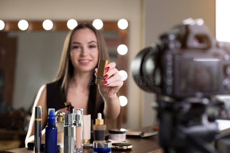 La ragazza allegra sta registrando il video circa i suoi prodotti di bellezza immagini stock