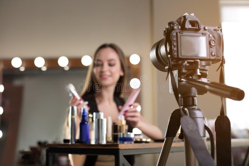 La ragazza allegra sta registrando l'esame dei cosmetici per il suo vlog fotografia stock libera da diritti