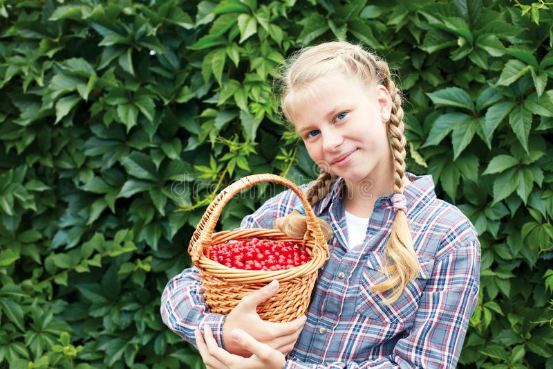 La ragazza allegra sta sui precedenti di una parete verde nel giardino, fotografia stock