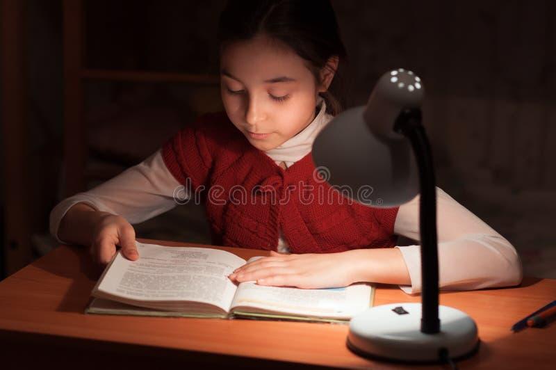 Ragazza allo scrittorio che legge un libro dall'indicatore luminoso della lampada fotografia stock libera da diritti