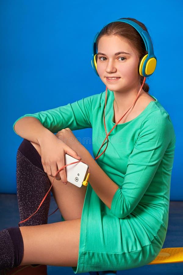 La ragazza ama ascoltare la canzone nel telefono la bella ragazza ama gli sport immagini stock
