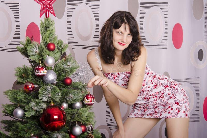 La ragazza appende sulla palla dell'albero fotografia stock