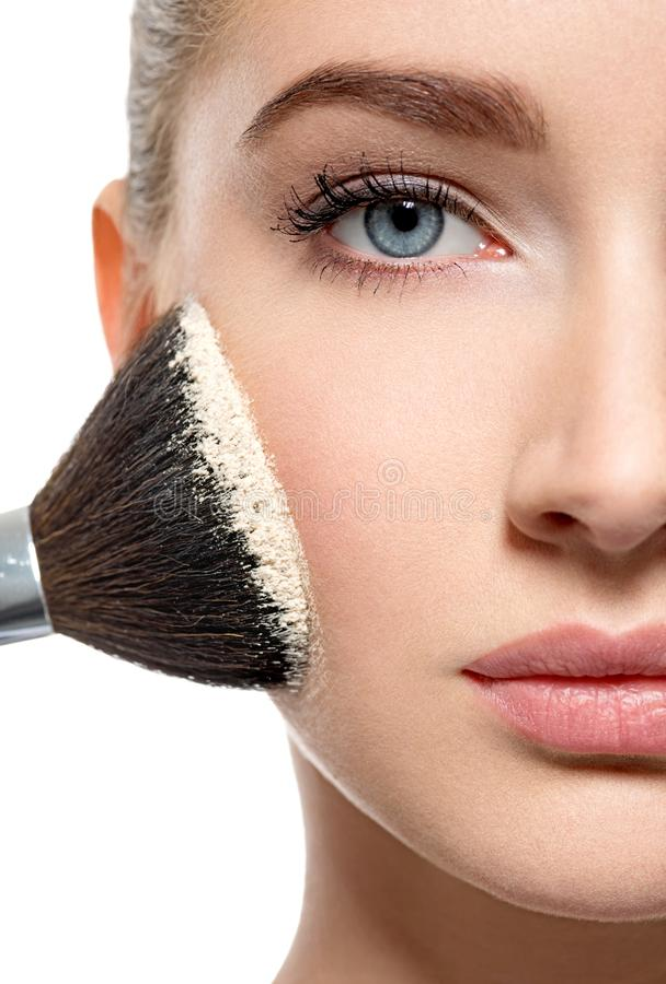 La ragazza applica la polvere sul fronte facendo uso della spazzola di trucco fotografia stock
