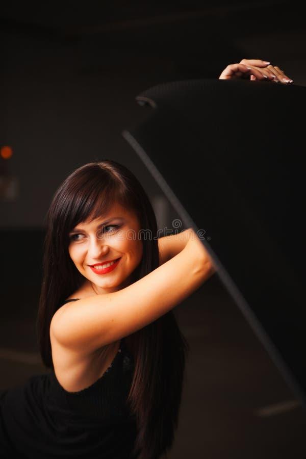 La ragazza apre il cappuccio dell'automobile fotografie stock libere da diritti
