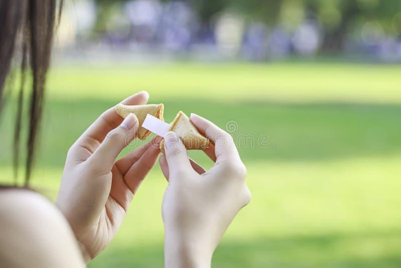La ragazza apre un biscotto di fortuna immagine stock libera da diritti