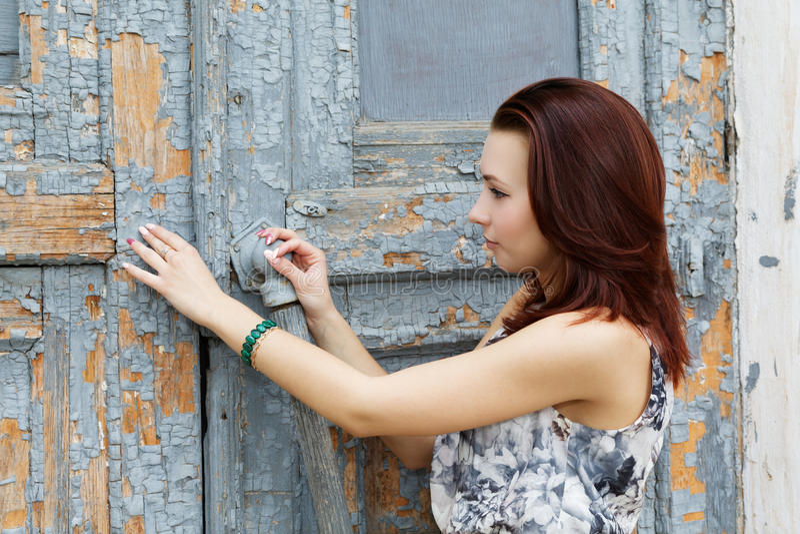 La ragazza apre una vecchia porta fotografia stock