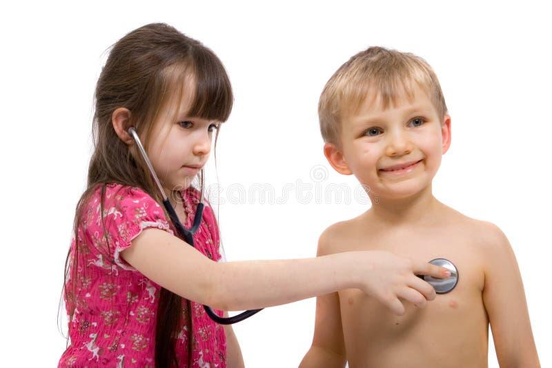 La ragazza ascolta con uno stetoscopio immagini stock libere da diritti