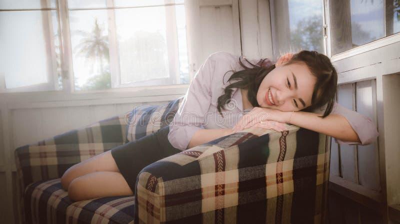 La ragazza asiatica è sorridente e collocante nello strato, trovantesi sul sofà fotografia stock