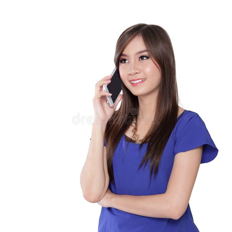 La ragazza asiatica che ha casuale discute a fondo il telefono cellulare immagini stock