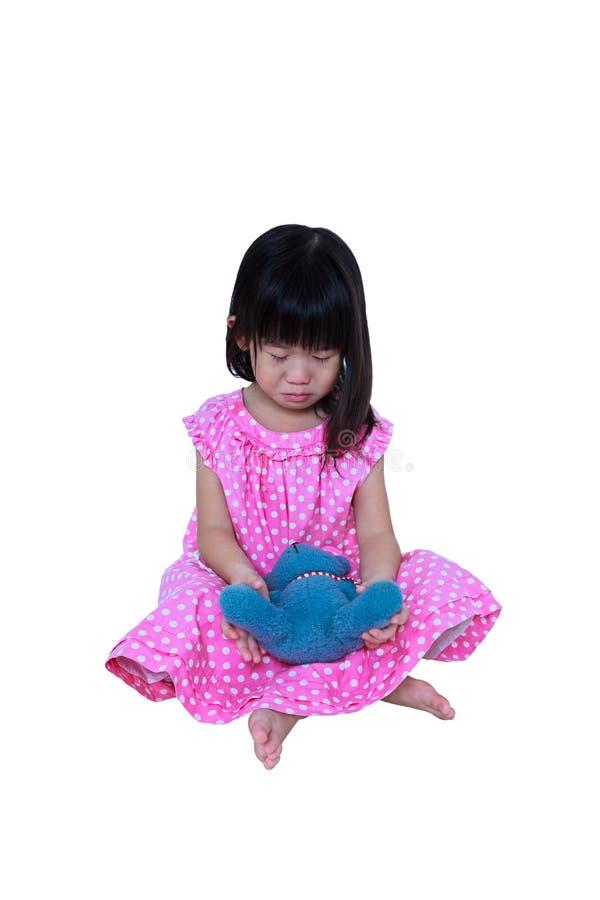 La ragazza asiatica che si siede con l'orso del giocattolo, rattrista e gridare Isolato su priorità bassa bianca immagine stock libera da diritti