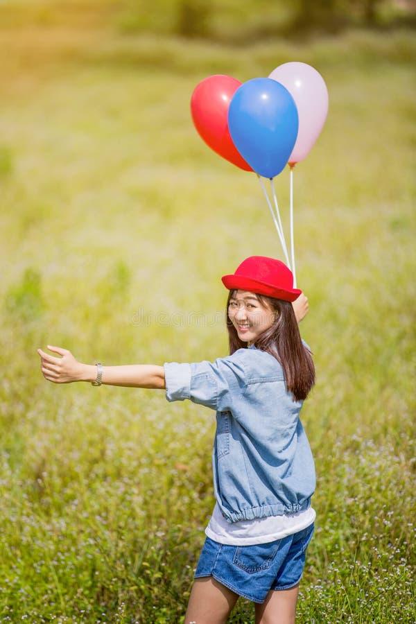 La ragazza asiatica con i palloni gioca in un campo immagine stock