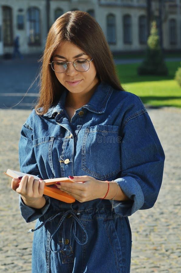 La ragazza asiatica con i vetri vestiti in un vestito del denim esamina un libro aperto fotografia stock libera da diritti