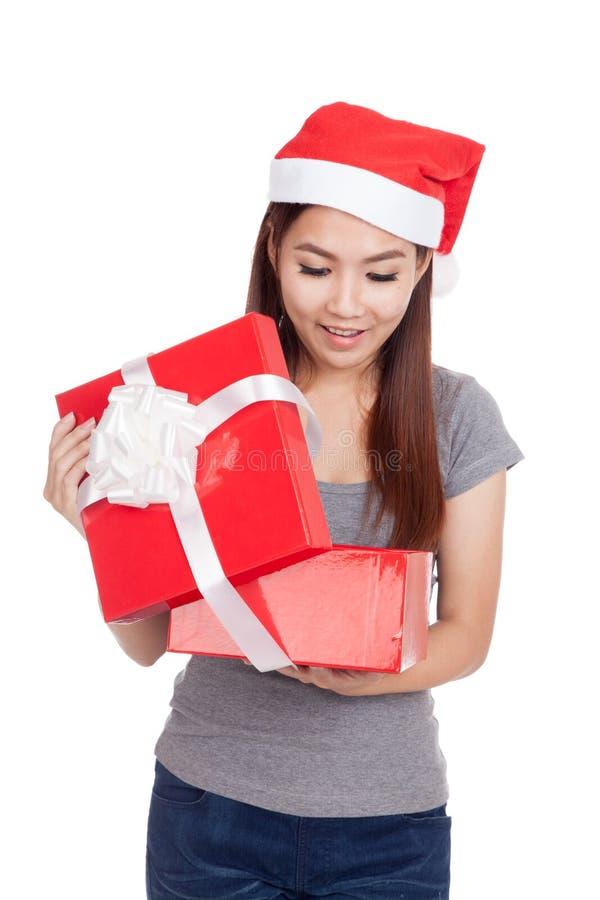 La ragazza asiatica con il cappello rosso di Santa apre un contenitore e un sorriso di regalo fotografie stock libere da diritti