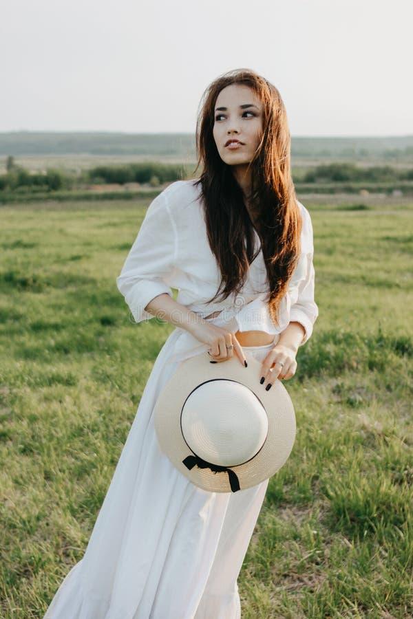 La ragazza asiatica dei bei capelli lunghi spensierati in vestiti e cappello di paglia bianchi gode della vita nel campo al tramo fotografia stock