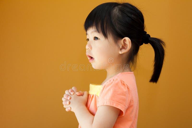 La ragazza asiatica del bambino del bambino sta pregando fotografia stock libera da diritti