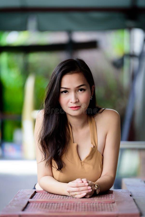 La ragazza asiatica del ritratto e graziosa ha rilassamento al caffè del caffè fotografie stock libere da diritti