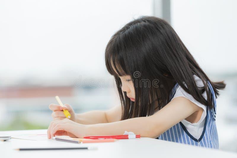 La ragazza asiatica disegna seriamente fotografie stock