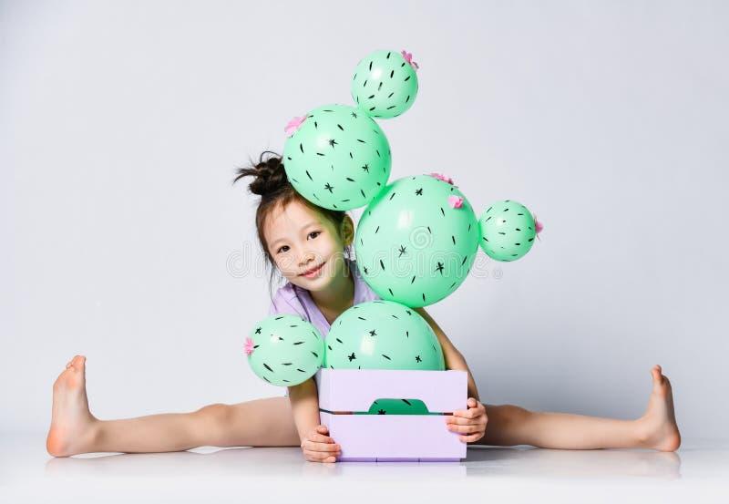 La ragazza asiatica divertente si siede con le gambe allungate dietro la scatola con il pallone del cactus e nelle sbirciate fuor fotografie stock libere da diritti