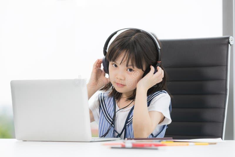 La ragazza asiatica indossa la cuffia fotografie stock libere da diritti